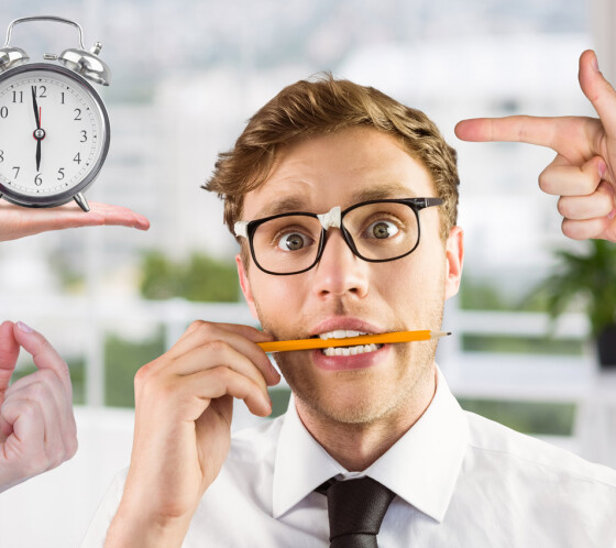 Conceptual image of worried businessman with hand pointing and alarm clock